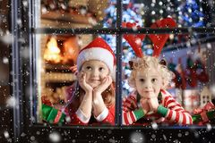 Child at Christmas tree. Kids at fireplace on Xmas. Children at Christmas tree and fireplace on Xmas eve. Family with kids celebrating Christmas at home. Boy and royalty free stock photo
