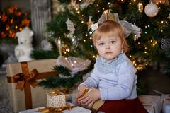 Child at christmas tree. The child is sitting with presents at the New Year tree Stock Image