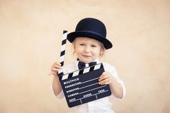 Child with clapper board playing at home stock photo