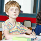 Child in class in elementary school. Smiling child in class in elementary school and writing lefthanded Royalty Free Stock Photo