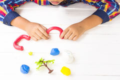 Child with Clay and using creativity for making red door of garden and etc.Top view and Zoom in. Stock Photos