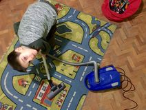 Child clean nursery with vacuum cleaner Royalty Free Stock Image