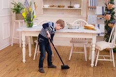 Child cleaning room with broom. Child cleaning kitchen. Little boy sweeping the floor. Pretty boy cleaning the kitchen with broom. Child cleaning room with stock photos