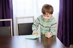 Child cleaning table in kitchen with rag. Boy child cleaning table in kitchen with rag Stock Photo