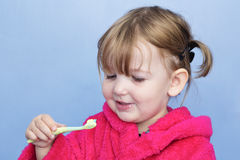 Child cleaning teeth. A young girl in a pink dressing gown against a light blue background. She's cleaning her teeth and has stopped to smile at the brush Royalty Free Stock Photos