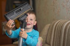 The child cleans the house with a vacuum cleaner stock photo