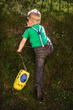 Child climb on the hill. Little boy holding toy car and climbing on the hill Royalty Free Stock Photography