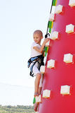 Child climbing. Caucasian child undergoin treatmant for cancer climbing a blow up castle at a fun fair Stock Image