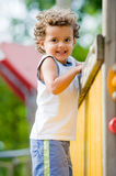 Child Climbing. A cute young kid playing on a climbing frame in a park stock photos