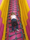 Child Climbing. Young girl climbing up a rope ladder on a boucny slide at the fun fair Stock Images