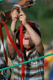 Child climbing in adventure playground. Portrait of young boy wearing helmet climbing. Child in a wooden abstacle course in adventure playground Royalty Free Stock Image