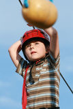 Child climbing in adventure playground. Portrait of young boy wearing helmet climbing. Child in a wooden abstacle course in adventure playground Royalty Free Stock Images