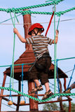 Child climbing in adventure playground. Portrait of young boy wearing helmet climbing. Child in a wooden abstacle course in adventure playground Royalty Free Stock Photography