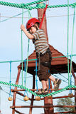 Child climbing in adventure playground. Portrait of young boy wearing helmet climbing. Child in a wooden abstacle course in adventure playground Royalty Free Stock Photos