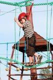 Child climbing in adventure playground Royalty Free Stock Photos