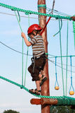 Child climbing in adventure playground. Portrait of young boy wearing helmet climbing. Child in a wooden abstacle course in adventure playground Stock Photography