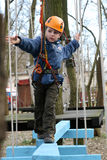 Child climbing in adventure playground. Portrait of 6 years old boy wearing helmet and climbing. Child in a wooden abstacle course in adventure playground Royalty Free Stock Photography