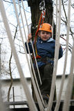 Child climbing in adventure playground. Portrait of 6 years old boy wearing helmet and climbing. Child in a wooden abstacle course in adventure playground Royalty Free Stock Photo