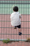 Child climbing fence stock photos