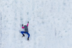 Child climbing frozen waterfall. Person child climbs up the icy rock. Child climbing frozen waterfall Royalty Free Stock Photography