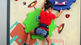 Child climbing a fun wall indoors. Video footage of a little girl climbing a fun wall indoors to train her courage, strength, endurance and agility while wearing stock video footage