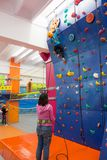 Child climbing an indoor artificial wall Stock Images