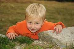 Child climbing. Little caucasian child climbing a rock Royalty Free Stock Photo