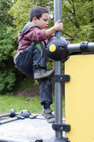 Child climbing at playground. Child climbing on a  playground equipment frame in a modern parkour playground Stock Photo