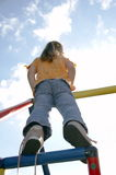 Child on climbing pole 04. Child on climbing pole from behind Stock Photo