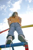 Child on climbing pole 04. Child on climbing pole from behind Stock Image