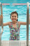 Child climbing pool ladder. Cute little girl climbing out of blue pool, smiling Stock Photo