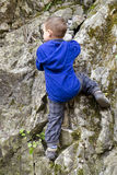 Child climbing a rock. Small child boy climbing and scrambling a rock in a nature Stock Images