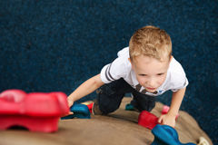 Child Climbing Rock Wall. Young boy climbing the play ground rock wall.  Intense look on the child's face as he climbs up the rock Royalty Free Stock Photos