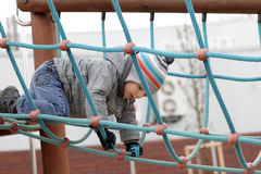 Child climbing on rope. At outdoor playground Royalty Free Stock Photography
