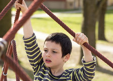Child climbing ropes at playground or in park Stock Photo