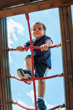 Child climbing ropes in a playground Stock Photos