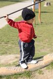 Child climbing up stairs on playground. Little baby boy stepping up stairs holding a rope over his head, spring time on playground Stock Photos
