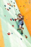 Child climbing up the wall. Smiling elementary child climbing up the wall Stock Photo