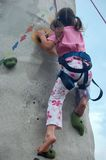 Child Climbing a Wall. Five years old girl is climbing a wall Stock Photo