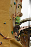 Child climbing wall. Young child climbing a training wall in a playground Stock Images
