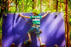 Child climbing on a wall in an outdoor climbing center in summer day.  Royalty Free Stock Images
