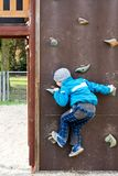 Child climbing a wall in a playground Stock Photography