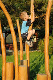 Child climbing wooden column. Young child climbing a wooden column, having fun on a playground Stock Photo