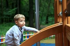 Child climbing on slide. Child climbing on wooden slide in summer park Royalty Free Stock Photography