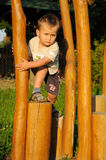 Child climbing wooden steps. Little child climbing steps on a playground and adhering to a wooden column Royalty Free Stock Photo