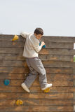 Child climbing a wooden wall royalty free stock image