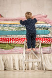 Child climbs on the bed - Princess and the Pea. Child climbs on the bed with lots of quilts - Princess and the Pea Royalty Free Stock Photo