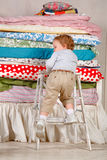 Child climbs on the bed - Princess and the Pea. Child climbs on the bed with lots of quilts - Princess and the Pea Royalty Free Stock Images