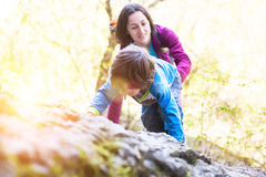 The child climbs on the boulder. A little boy climbs a big stone. Mom helps son to climb up Stock Photo
