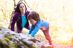 The child climbs on the boulder. A little boy climbs a big stone. Mom helps son to climb up Stock Photos
